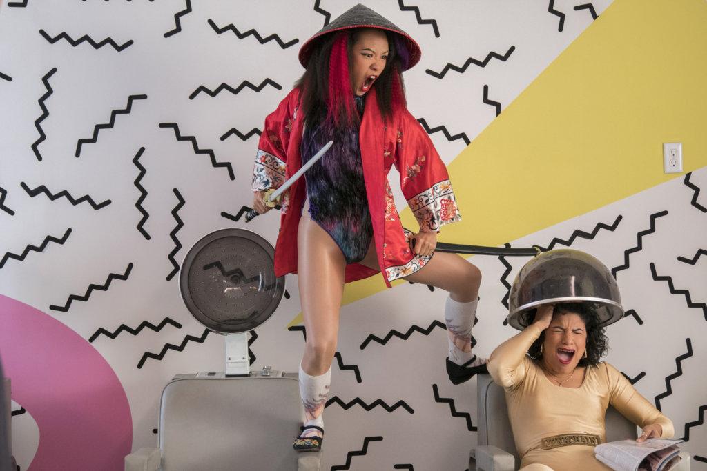 Jenny 'Fortune Cookie' Chey (Ellen Wong) and Yolanda 'Junkchain' Rivas (Shakira Barrera) filming a 'GLOW' promo